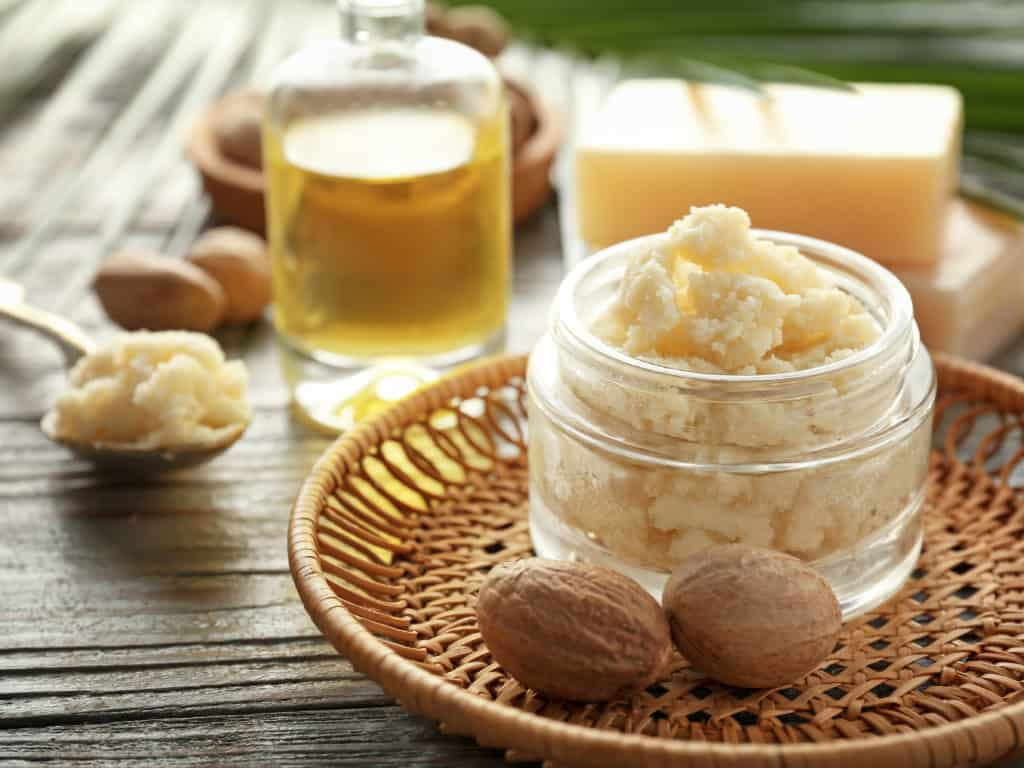 Jar with shea butter on wooden background